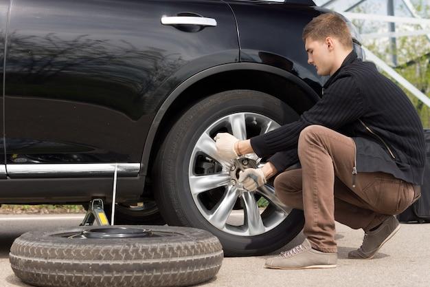 Mechanik zmieniający koło podczas pomocy drogowej