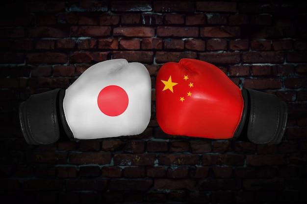 Mecz bokserski. konfrontacja między japonią a chinami. chińskie i japońskie flagi narodowe na rękawicach bokserskich. rywalizacja sportowa między dwoma krajami. pojęcie konfliktu polityki zagranicznej.