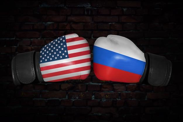 Mecz bokserski. konfrontacja między usa a rosją. rosyjskie i amerykańskie flagi narodowe na rękawicach bokserskich. rywalizacja sportowa między dwoma krajami. pojęcie konfliktu polityki zagranicznej.