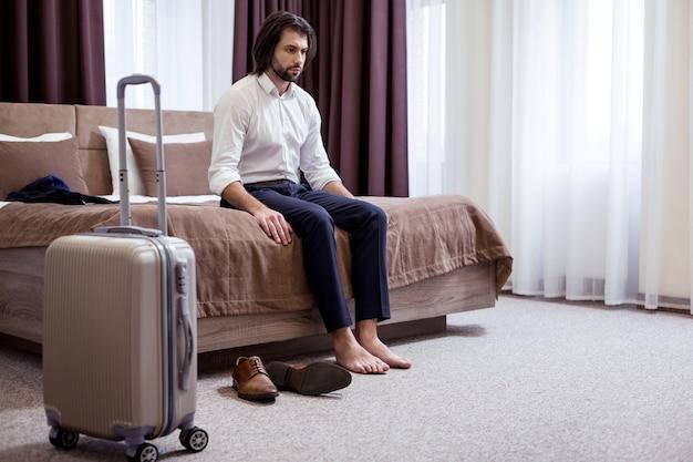 Męcząca droga. miły przystojny mężczyzna czuje się bardzo wyczerpany wchodząc do swojego pokoju hotelowego