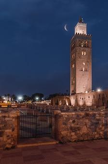 Meczet koutoubia nocą świecący pod półksiężycem w marrakeszu, maroko
