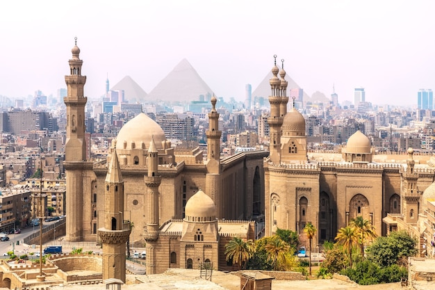 Meczet-madrasa sułtana hassana i piramidy w tle, kair, egipt.