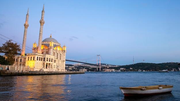 Meczet ortakoy, cieśnina bosfor i most wieczorem, łódź na pierwszym planie, budynki położone na wzgórzach w stambule w turcji