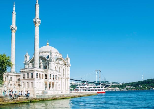 Meczet ortakoy w oddali na tle błękitnego nieba w stambule.