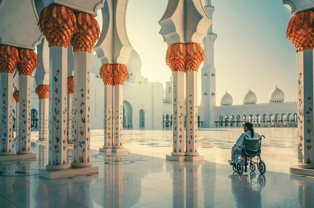 Meczet szejka zayeda. niepełnosprawny mężczyzna siedzi na wózku inwalidzkim. mężczyzna modli się w meczecie. abu dabi
