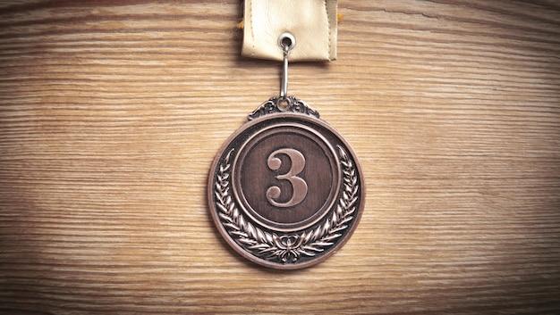 Medal dla zwycięzcy na drewnianym tle.