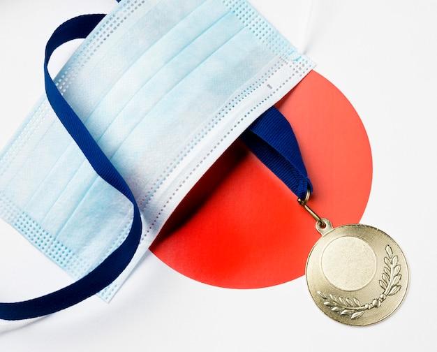 Medal sportowy leżący płasko obok maski medycznej