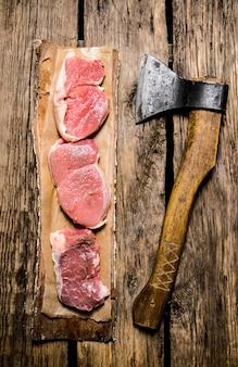 Medaliony z surowego mięsa na drzewie z siekierą. na drewnianym tle. widok z góry