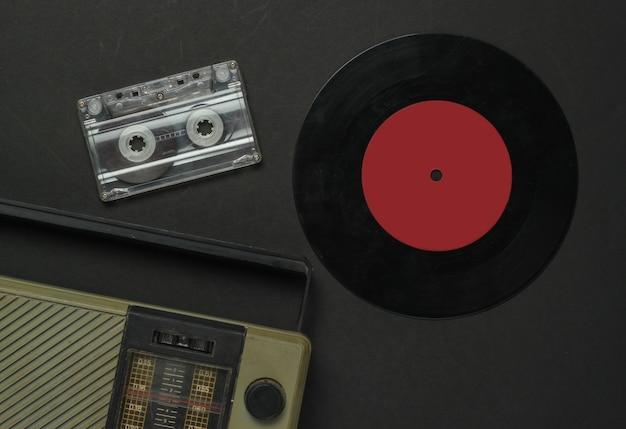 Media retro. odbiornik radiowy, płyta winylowa, kaseta magnetofonowa na czarnym tle. widok z góry.