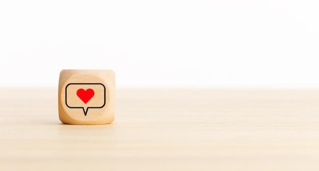 Media społecznościowe ikona serca na drewnianym bloku. skopiuj miejsce.