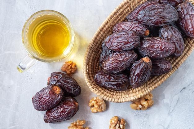 Medjool daktyle w drewnianym koszu z orzechami włoskimi i herbatą na stole, widok z góry. wysoce pożywne owoce zwiększają ilość mleka matki karmiącej.