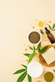 Medycyna alternatywna, kosmetyki naturalne. olej cbd i konopie pozostawia kosmetyki widok z góry na pomarańczowym tle, płaskie lay