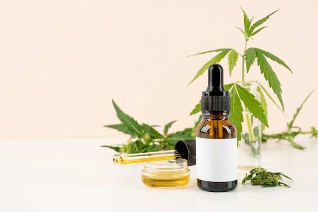 Medycyna alternatywna, kosmetyki naturalne. olej cbd i konopie pozostawiają kosmetyki widok z przodu na pomarańczowym tle, kopia przestrzeń