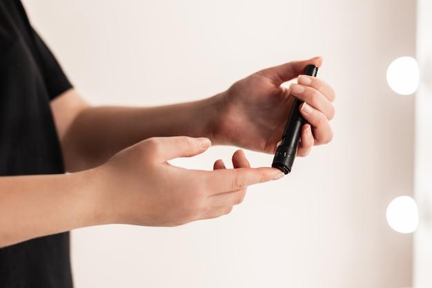 Medycyna, cukrzyca, glikemia, koncepcja opieki zdrowotnej i ludzi - zbliżenie rąk kobiety za pomocą lancetu na palcu, aby sprawdzić poziom cukru we krwi przez glukometr. test na cukrzycę w domu