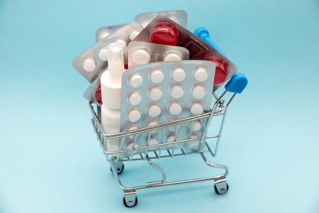 Medycyna farmaceutyczna. wózek na zakupy z pigułkami i zaopatrzeniem medycznym na błękicie