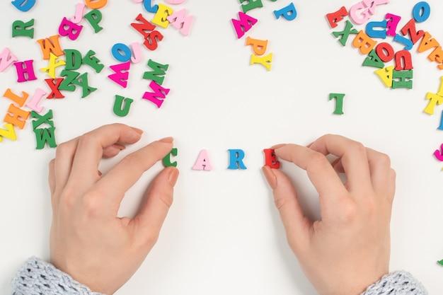 """Medycyna i opieka zdrowotna. kobiece dłonie układają słowo """"care"""" z kolorowych liter"""