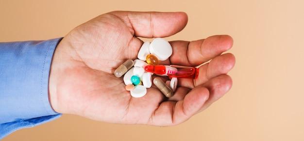 Medycyna i zabiegi. ręka człowieka z pigułkami. terapia lekami. tabletki przepisane przez lekarza.