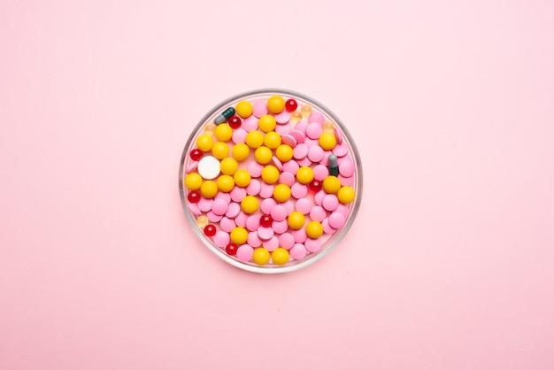 Medycyna kolorowe talerze różowe tło zbliżenie antybiotyki