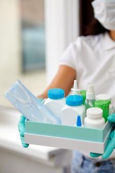 Medycyna kurier w masce i rękawiczkach z zakupami pigułek medycznych podczas zapobiegania koronowirusowi, koncepcja bezpiecznego domu i kwarantanny, wolontariusz z darowizną.