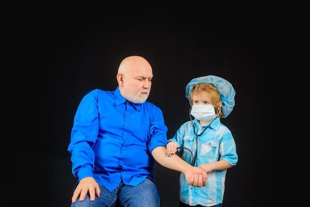 Medycyna leczenie leczenie domowe lekarz gra dzieciak bawi się lekarz z dziadkiem chłopiec lekarz bawi się
