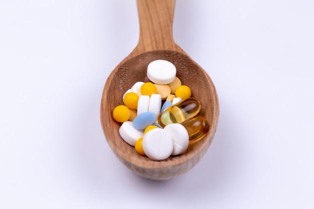 Medycyna, pigułki i lek w drewnianej łyżce na białym tle z kopii przestrzenią