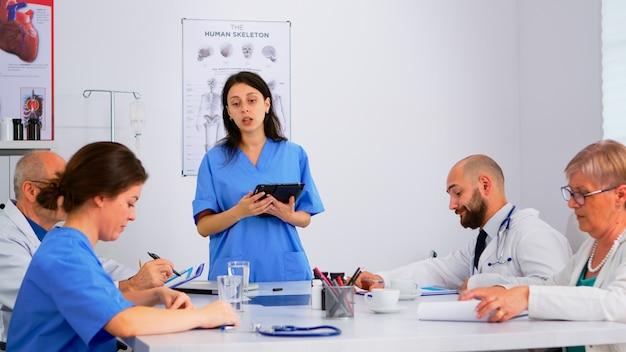 Medycyna, spotkanie i planowanie z udziałowcami w biurze szpitala, siedząc przy biurku. lekarze i pielęgniarki wspólnie przeprowadzają burzę mózgów, diagnozują lekarzy i prezentują dane za pomocą tabletu