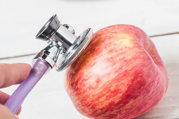 Medycyna stetoskop i jab? ko owoców na drewnianym tle. zdrowy styl? ycia koncepcji obrazu.