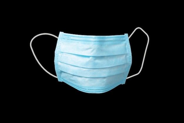 Medyczna antybakteryjna ochronna niebieska maska na czarną ścianę, miejsce na kopię. koncepcja profilaktyki chorób układu oddechowego i wirusów.