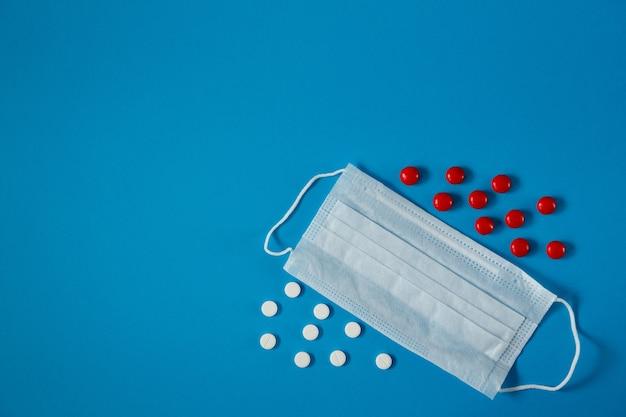 Medyczna maska na twarz i pigułki na niebieskim tle