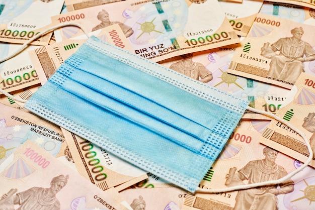 Medyczna maska na twarz i stos uzbeckich sum uzbeckich pieniędzy i covid19