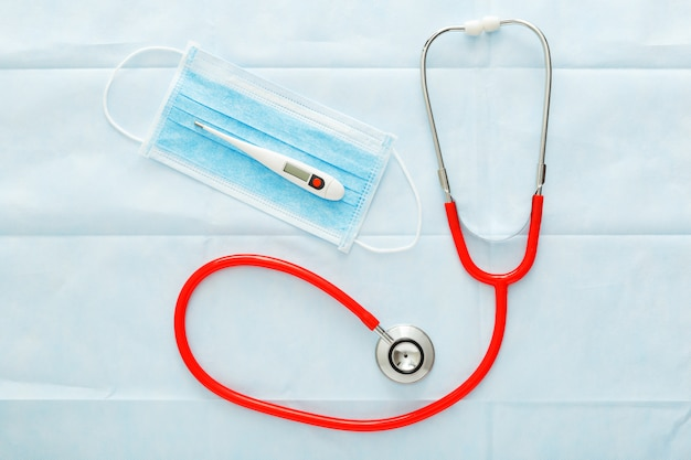 Medyczna maska termometr czerwony stetoskop, chirurgiczna maska ochronna na niebiesko.
