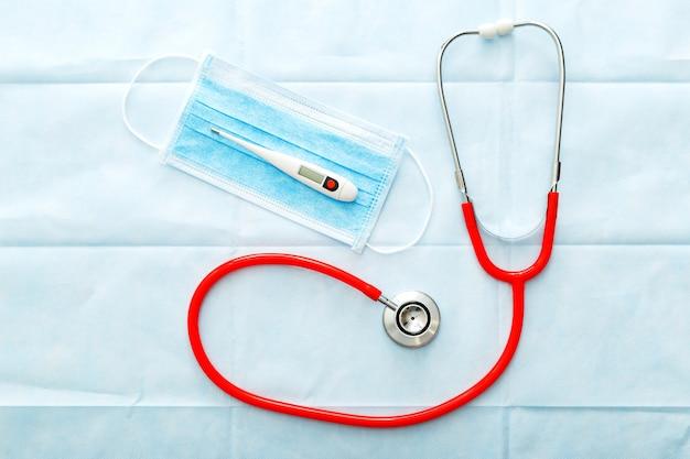 Medyczna maska termometr czerwony stetoskop, chirurgiczna maska ochronna na twarz. profesjonalny sprzęt lekarzy. pojęcie medyczne opieki zdrowotnej. zapobieganie koronawirusowi covid-19.