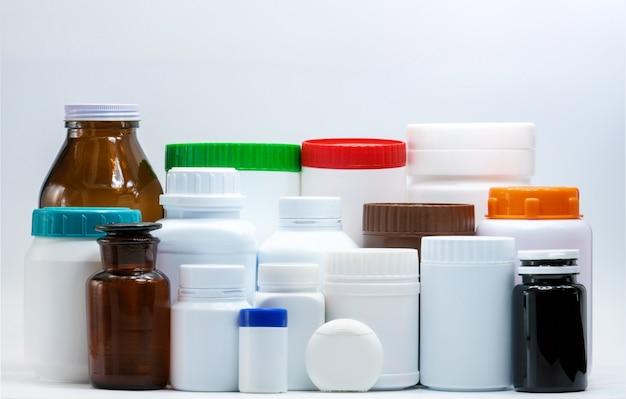 Medyczna plastikowa i bursztynowa butelka na białym tle z pustą etykietką. przemysł opakowań farmaceutycznych. pojemnik na butelki z witaminami i suplementami. butelka z tabletkami z pomarańczowym, zielonym, niebieskim i czerwonym wieczkiem.