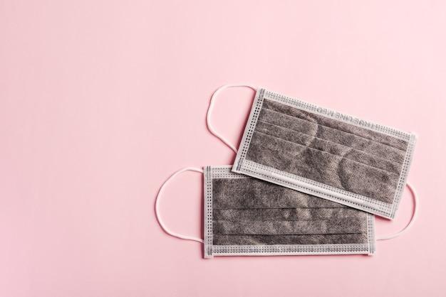 Medyczna węglowa maska ochronna na twarz na białym tle na różowym tle. bezpieczeństwo medyczne zapobieganie koronawirusowi lub covid-19