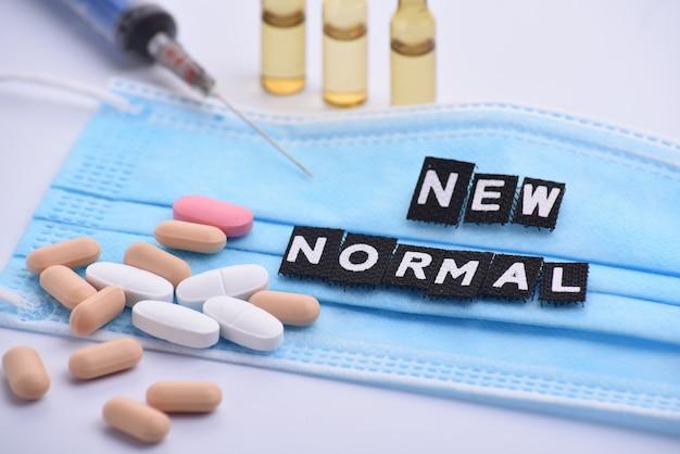 Medyczne ampułki do wstrzykiwań, wiele tabletek, strzykawka i maska medyczna z napisem new normal. leki i leczenie chorób.