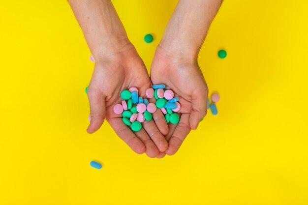 Medyczne kolorowe pigułki przy dzieciak rękami na żółtym tle z kopii przestrzenią