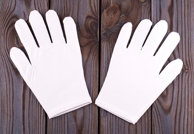 Medyczne kosmetyczne bawełniane białe rękawiczki na drewnianym stole