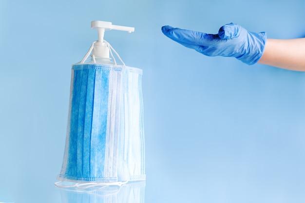 Medyczne maski na twarz, jednorazowa chirurgiczna maska ochronna na żelu z alkoholem w butelce do dezynfekcji rąk lekarza w rękawiczkach.