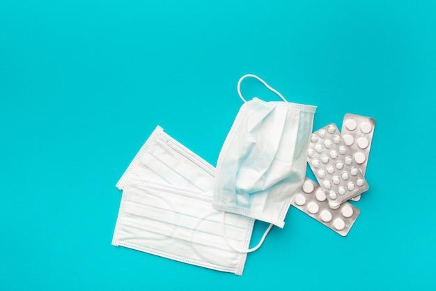 Medyczne maski ochronne i farmaceutyczne opakowania z pigułkami na niebieskim jasnym tle. koncepcja ochrony zdrowia przed wirusem. skopiuj miejsce