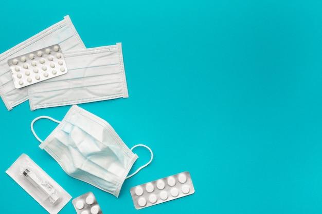 Medyczne maski ochronne, jednorazowa strzykawka w sterylnym opakowaniu i farmaceutyczne opakowanie z pigułkami na papierze, niebieskie jasne tło. koncepcja ochrony zdrowia przed wirusem. skopiuj miejsce