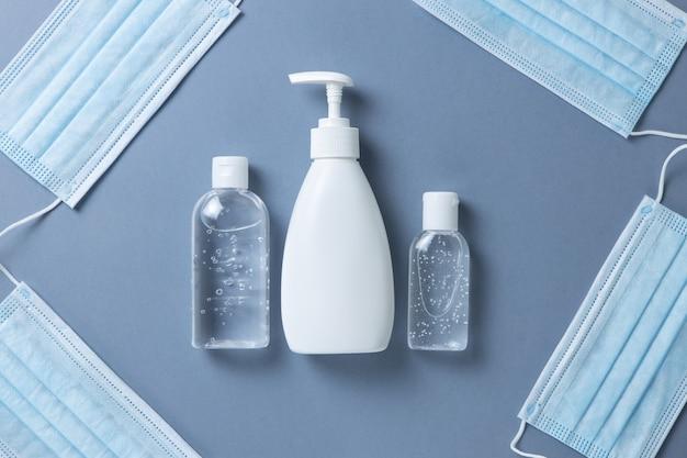 Medyczne ochronne, niebieskie maski na twarz, żel odkażający, mydło w płynie do rąk na szarej ścianie, zbliżenie, płaskie, minimalne. koncepcja higieny, sprzęt ochronny, zapobieganie rozprzestrzenianiu się infekcji wirusowych.