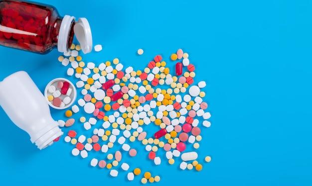 Medyczne pigułki i pastylki rozlewa się z butelki narkotyków na niebieskim stole