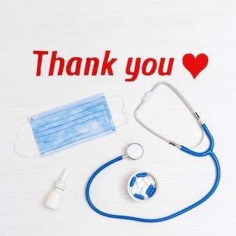 """Medyczne rzeczy na stole czerwone serce i tekst """"dziękuję"""" na białym drewnie"""