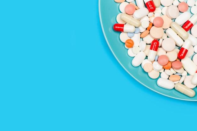 Medyczne tabletki i kapsułki w niebieskim talerzu na niebieskim tle