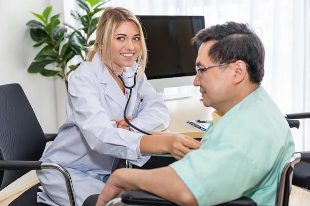 Medyczni profesjonaliści kaukaska kobieta egzamininuje starszego mężczyzna pacjenta z stetoskopem w sala szpitalnej.