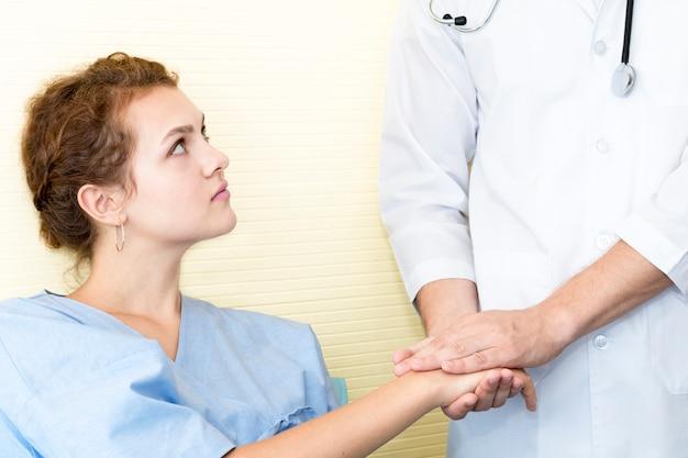 Medyczni profesjonaliści obsługują uspokajać i dyskutować z młodą kobietą martwią się pacjenta.