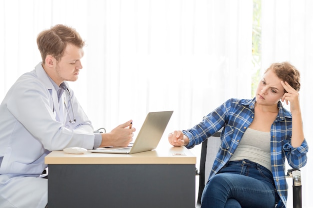 Medyczni profesjonaliści obsługują uspokajać i opowiadać z młoda kobieta stresu pacjentem.