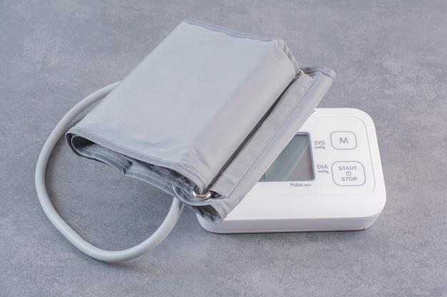 Medyczny elektroniczny tonometr na marmurowym stole.