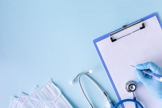 Medyczny pojęcie na błękitnym tle. stetoskop, pigułki, tablet, notatnik, kartka papieru, długopis. rękawiczki medyczne. maska medyczna. skopiuj miejsce