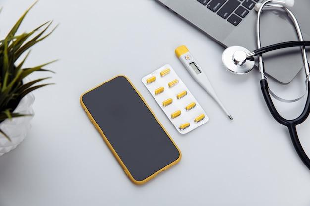 Medyczny pulpit ze stetoskopem, pigułkami, termometrem, smartfonem i laptopem